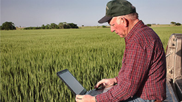 A landowner works on a laptop while sitting near cropland.