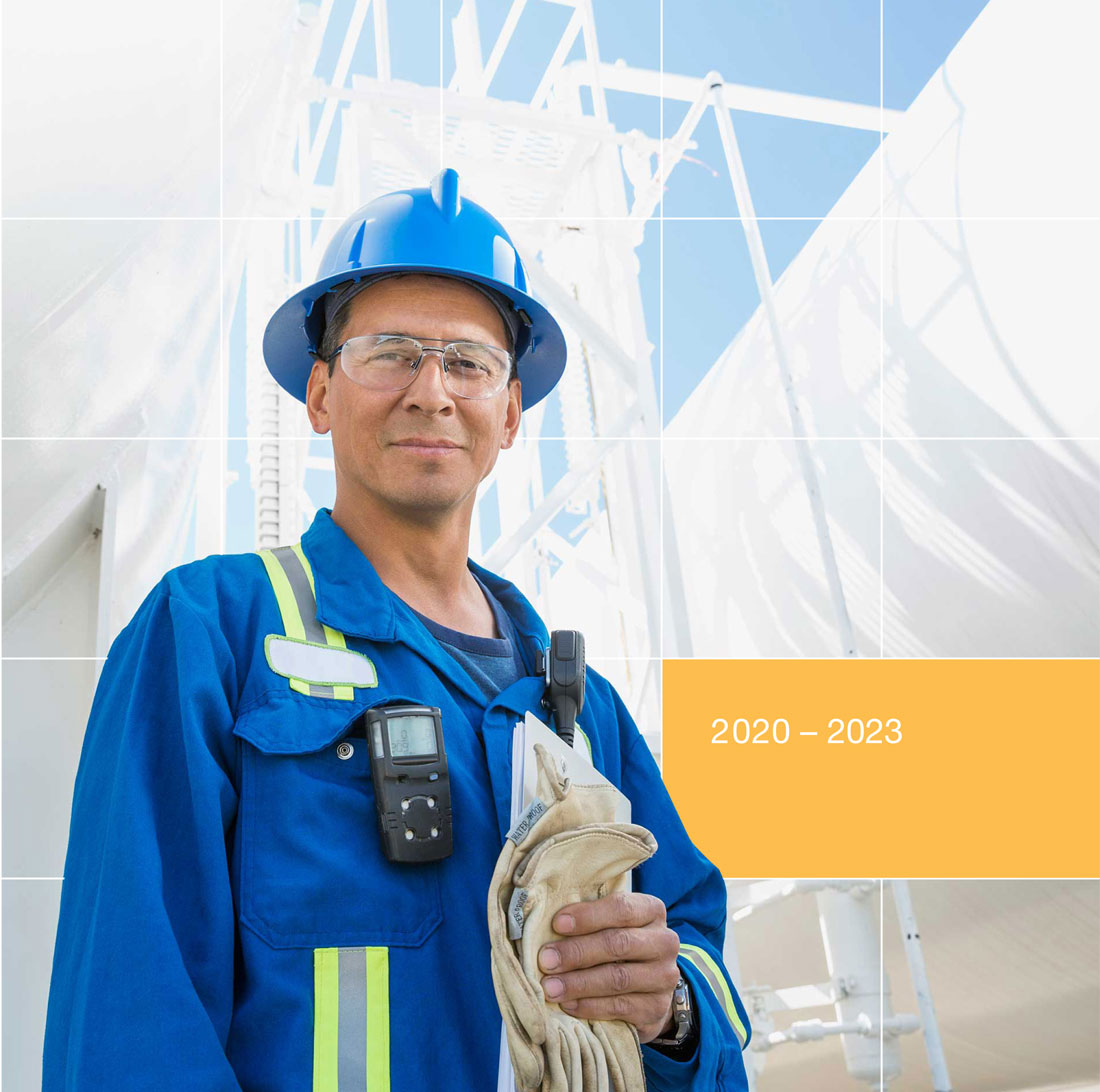 Male employee wearing PPE, holding gloves with whiteinfrastructure in the background.