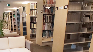 Several rows of bookshelves stretch back alongside some chairs in the CER library