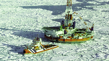 A small ship tows a floating offshore drilling rig through the ice