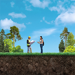 Two people standing in a field surrounded by trees and talking. One is male wearing a safety vest and holding a map. The other is female looking through a binder of notes.