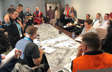 About 15 to 20 people in a room and gathered around a table. They are from the CER, the company, and local authorities working together in unified command to practice a response to an emergency.