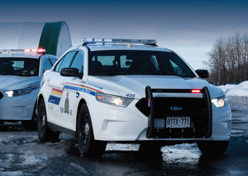Front view of two RCMP cruiser in rural environment